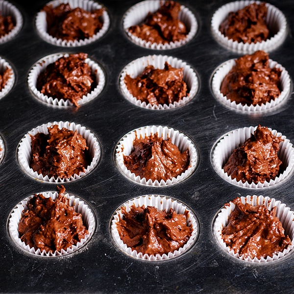 Filling a mini muffin tin with batter to make Double Chocolate Muffins.