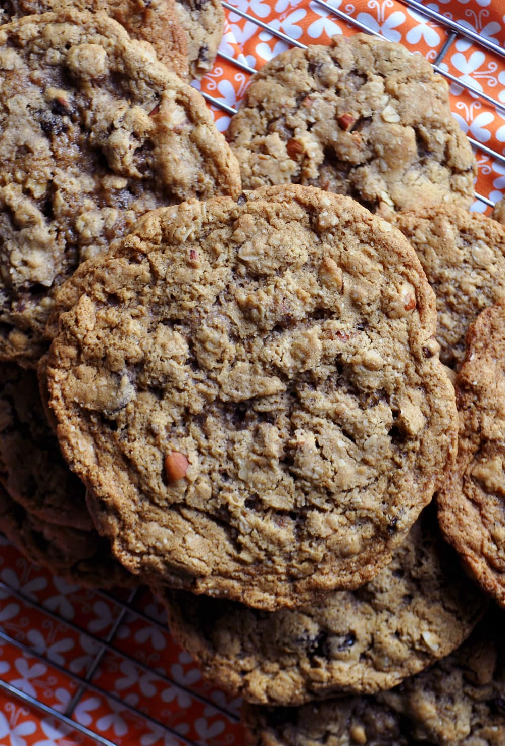 A pile of giant chewy oatmeal raisin cookies. | ofbatteranddough.com