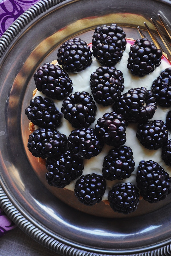 A close-up picture of a blackberry custard fruit tart with amaretto.