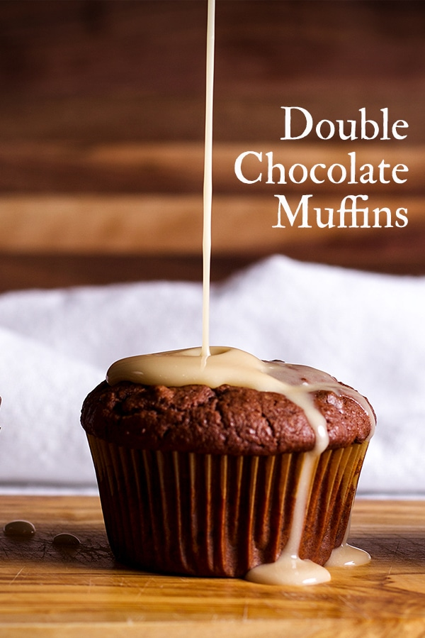 Pouring vanilla glaze over a chocolate muffin.