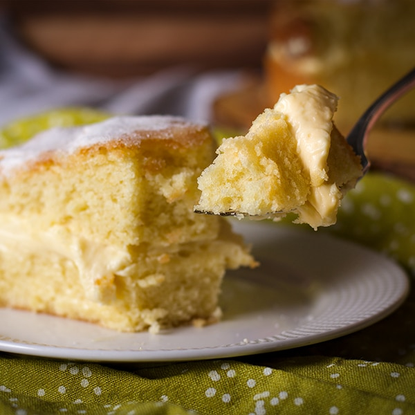 Taking a bite of a slice of Olive Oil Cake filled with Lemon Mascarpone Pastry Cream.