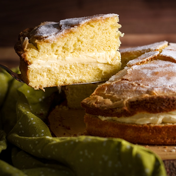 Serving a slice of Olive Oil Cake with Lemon Mascarpone Pastry Cream filling.