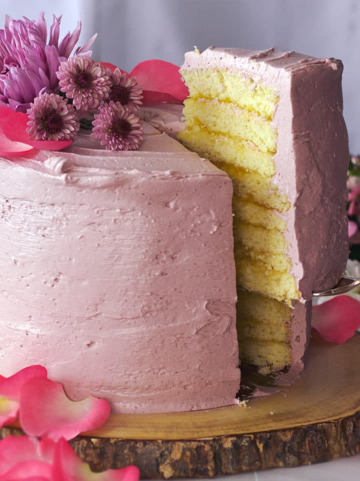 Serving a slice of Lemon Layer Cake with Blackberry Italian Meringue Buttercream