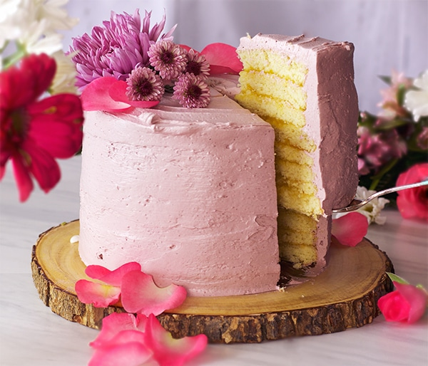 Serving a slice of Lemon Layer Cake with Blackberry Italian Meringue Buttercream