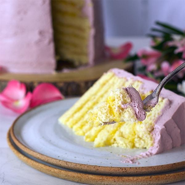 Taking a bite of Lemon Layer Cake with Blackberry Italian Meringue Buttercream