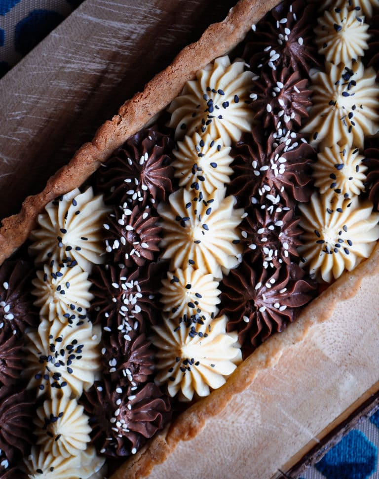 A black and white chocolate tahini tart with alternating stripes of white and dark chocolate filling.