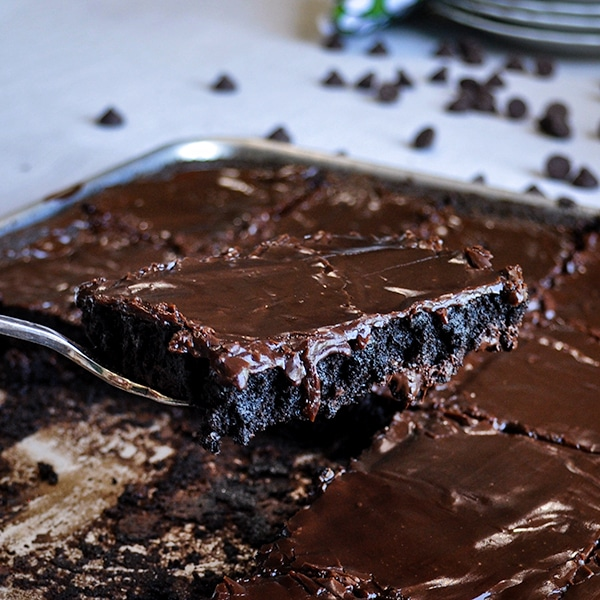 Serving a brownie from a large sheet pan of frosted brownies.