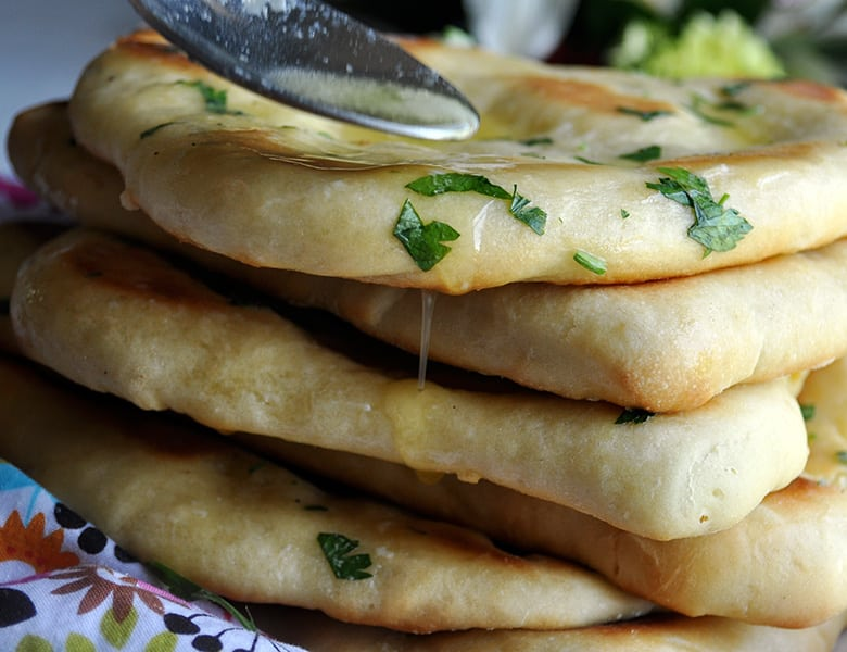 Drizzling butter over homemade garlic naan breads.