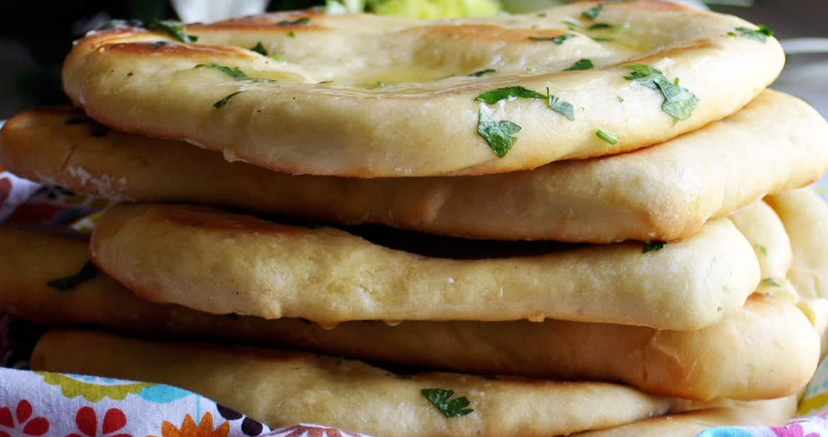 A stack of homemade garlic naan breads.