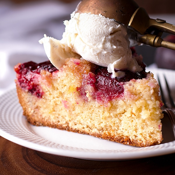 A slice of almond plum cake topped with a scoop of vanilla ice cream,.