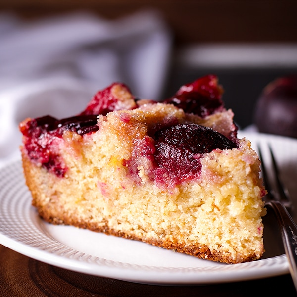 A slice of Almond Plum Cake on a plate with a fork.