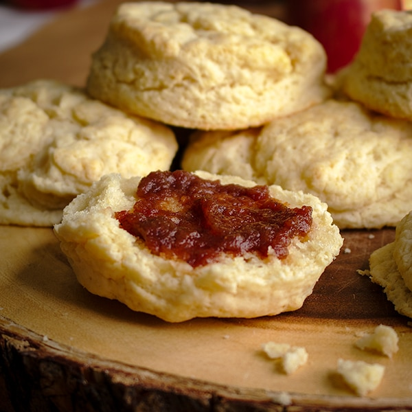 A cream biscuit, cut in half and spread with homemade apple butter.