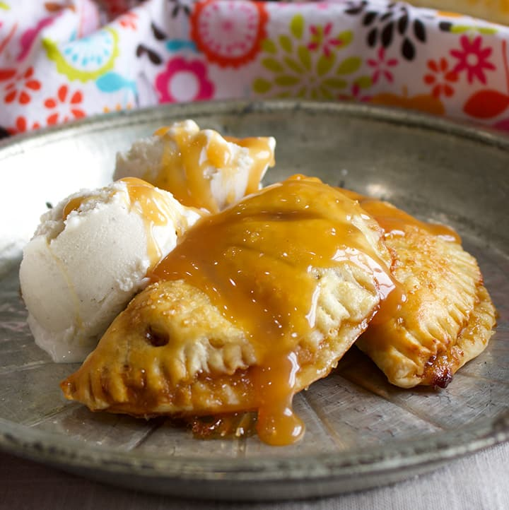 A plate of apple butter and pastry cream hand pies with vanilla ice cream and caramel sauce.