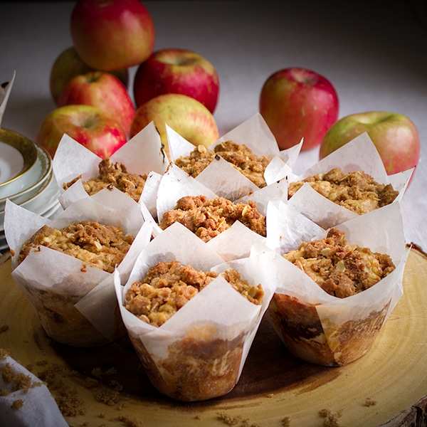 A wood tray with 7 apple cinnamon muffins on it and apples in the background.