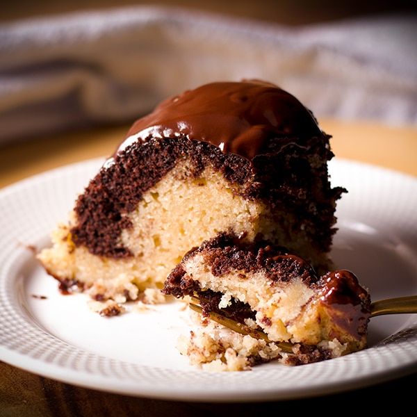 A slice of marble cake with chocolate glaze on a white plate with a gold fork.