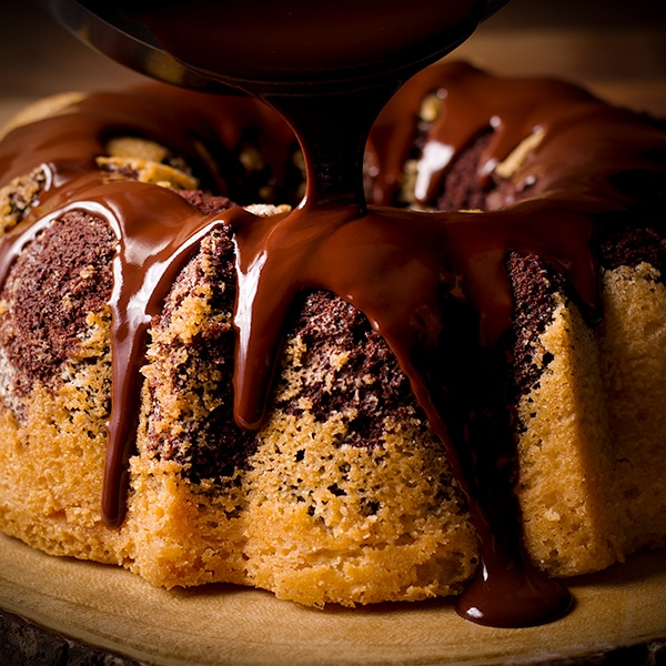 Pouring chocolate glaze over a freshly baked marble cake.