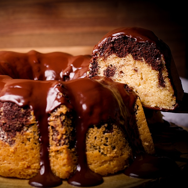 Serving a slice of marble cake covered in chocolate glaze.