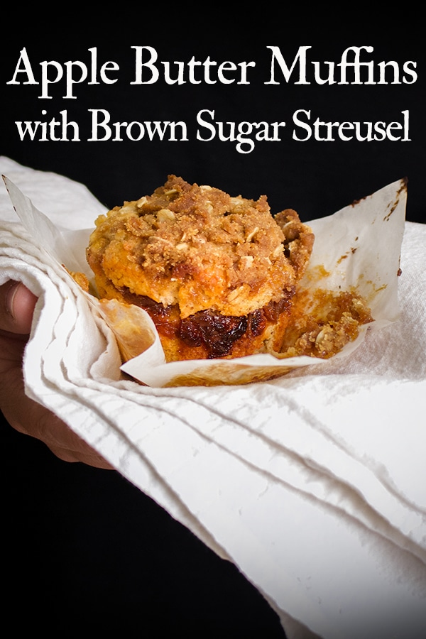Someone holding a warm apple cinnamon muffin with brown sugar streusel.
