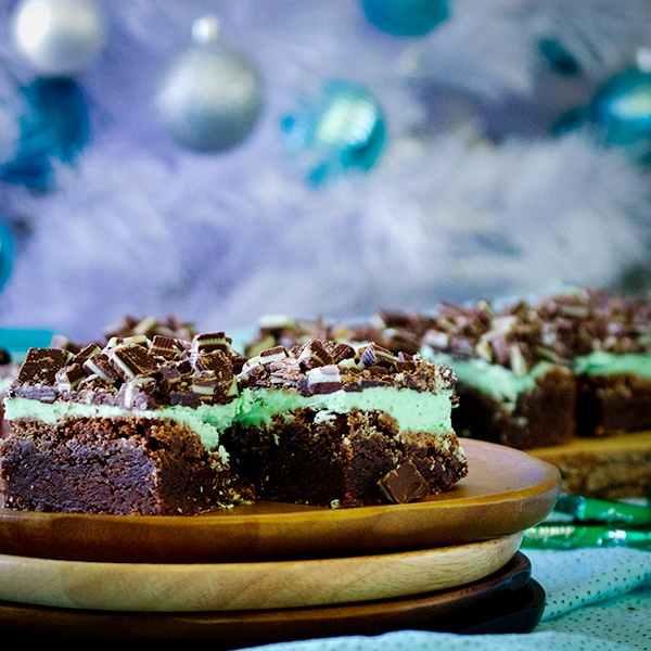 Two chocolate mint brownies on a plate.