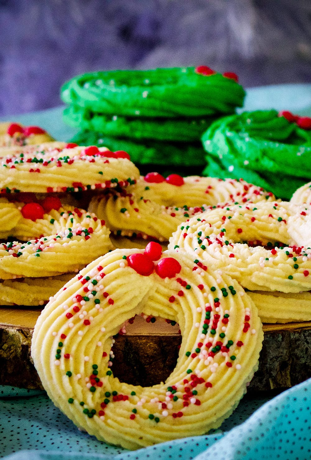 A tray stacked with Spritz cookies shaped like Christmas wreaths.