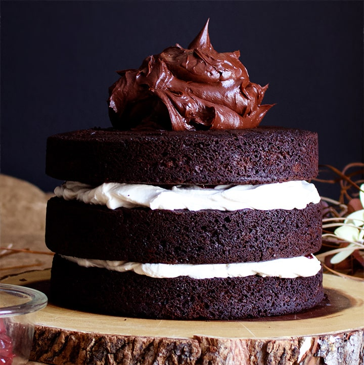 Chocolate Ganache topping Black Forest Cake made with layers of Devil's Food Cake, whipped cream and cherries.