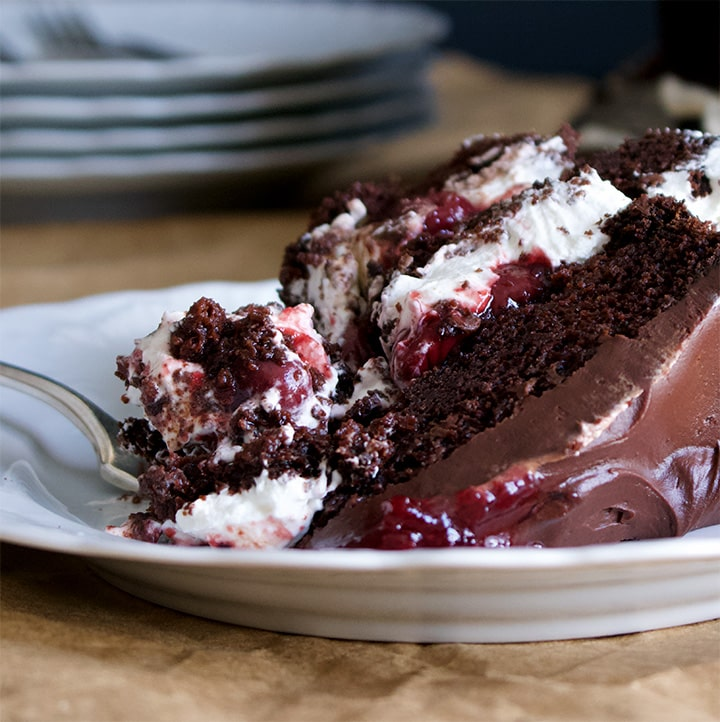 A piece of Black Forest Cake made with layers of Devil's Food Cake, whipped cream and cherries on a plate.
