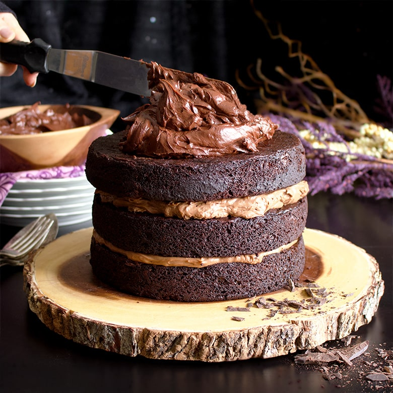 Spreading chocolate Ganache over Chocolate Blackout Cake.