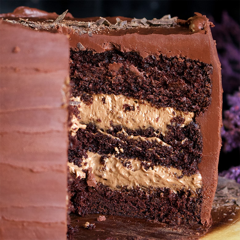 The inside of a chocolate blackout cake showing three layers of Devil's Food cake, chocolate pastry cream and chocolate ganache.