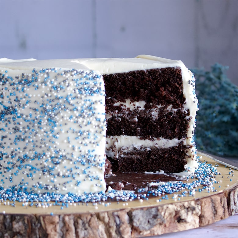 Three layer Chocolate Devil's Food Cake iced with Cream Cheese Buttercream and decorated with blue sprinkles.