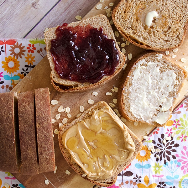 Slices of homemade whole wheat bread covered in jam, peanut butter, and butter.