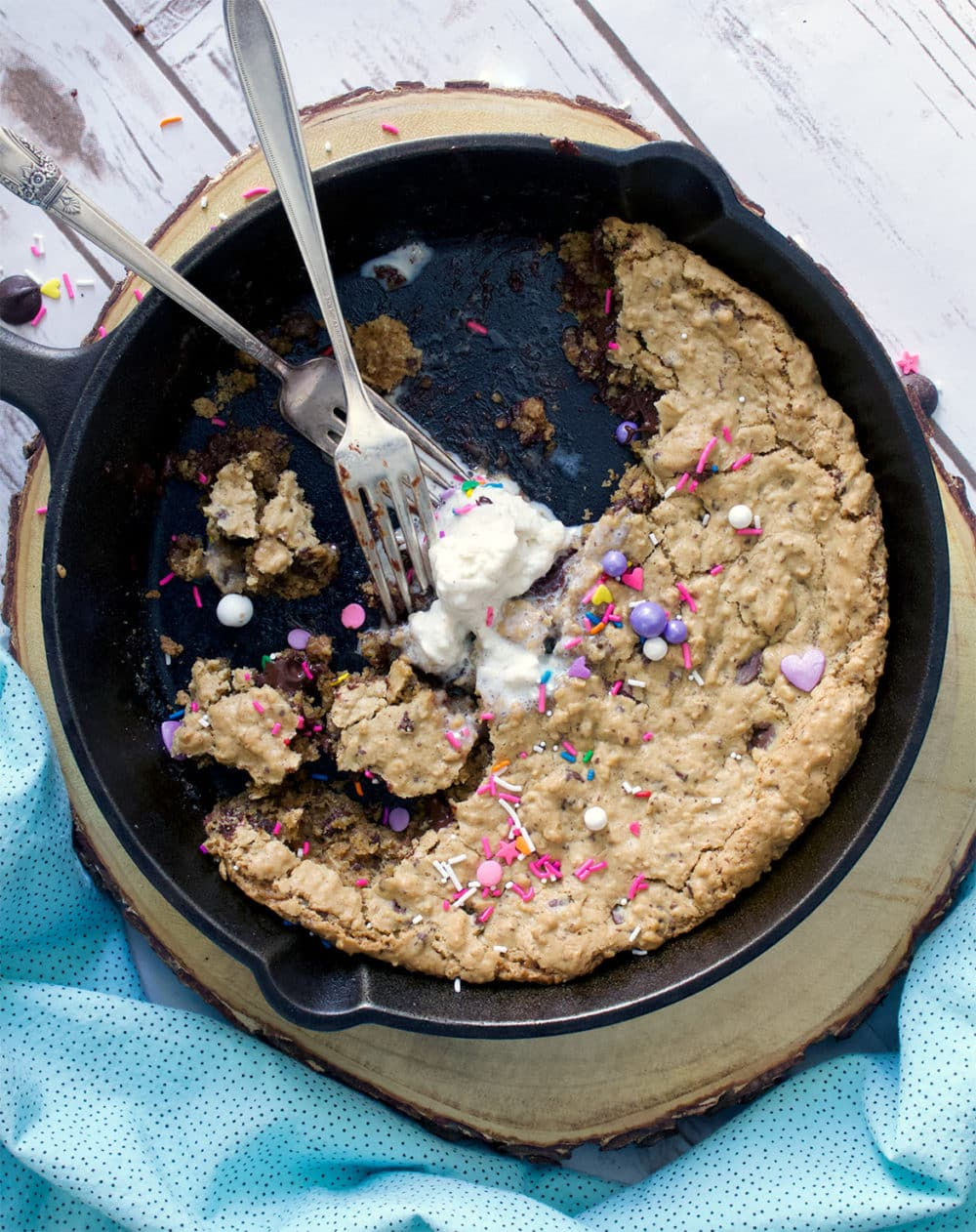 A half eaten skillet cookie with chocolate chips and oatmeal, ice cream and sprinkles.