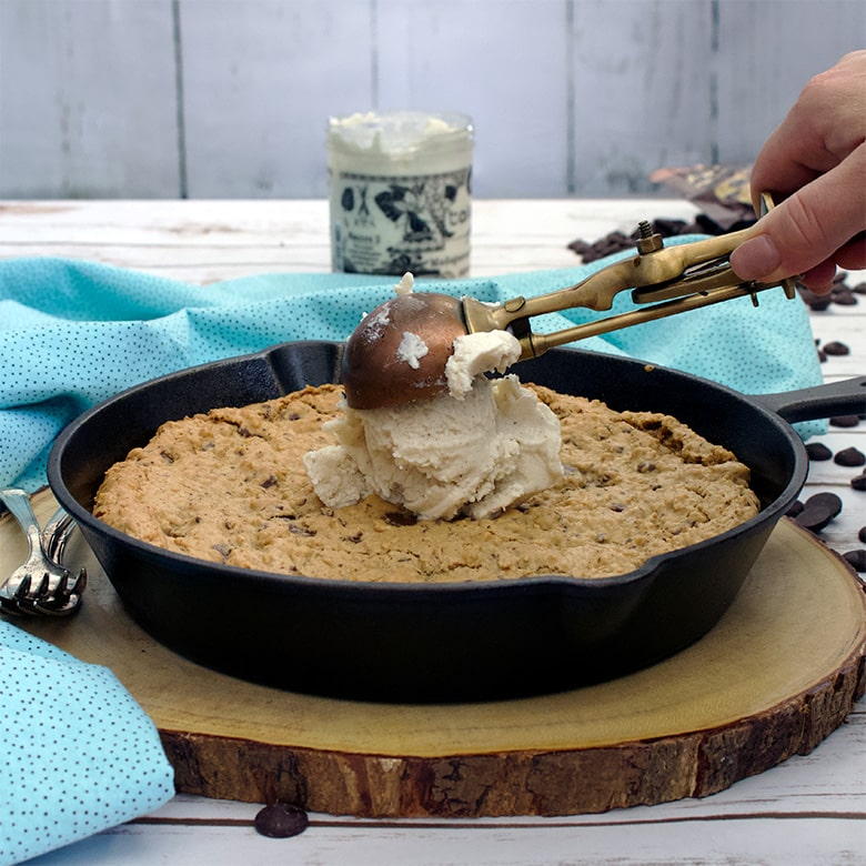 Adding a scoop of vanilla ice cream to the center of a fresh from the oven chocolate chip oatmeal skillet cookie.