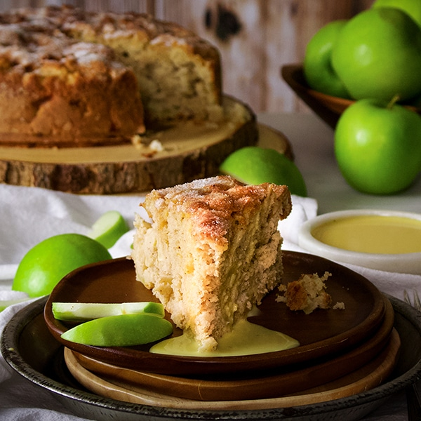 A slice of Irish Apple Cake on a plate with Custard Sauce.