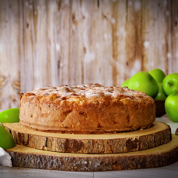 An Irish apple Cake on a wooden cake stand surrounded by green apples.