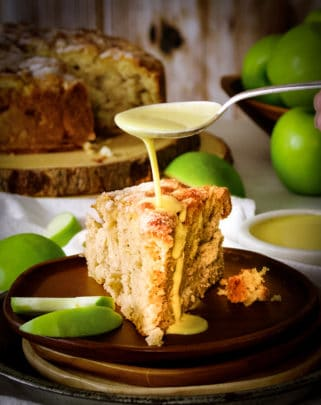 Drizzling a spoonful of custard sauce over a slice of Irish Apple Cake.