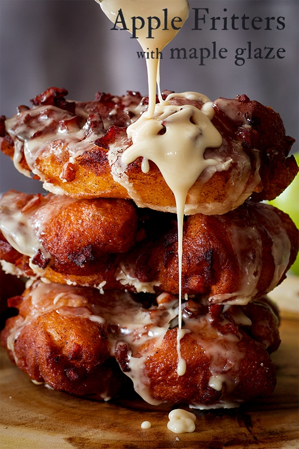 Drizzling Maple Glaze over a stack of three homemade Apple Fritter Doughnuts