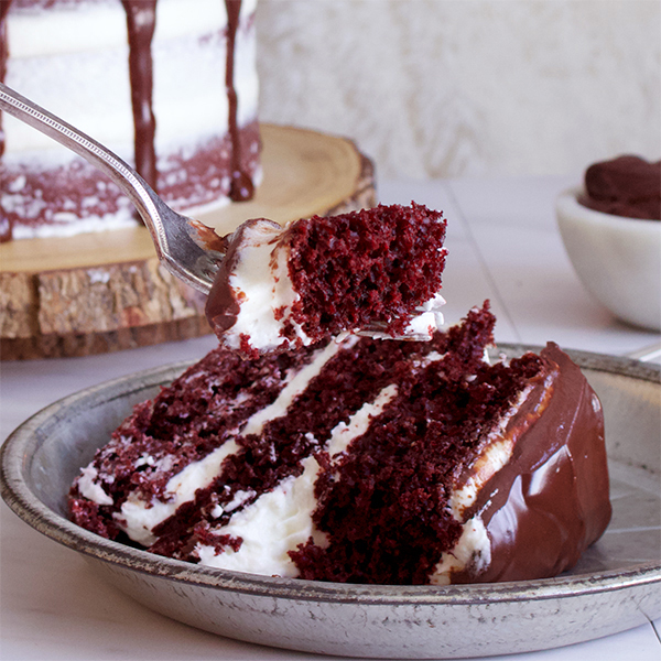 Taking a bite of red velvet cake with cream cheese buttercream and chocolate ganache.