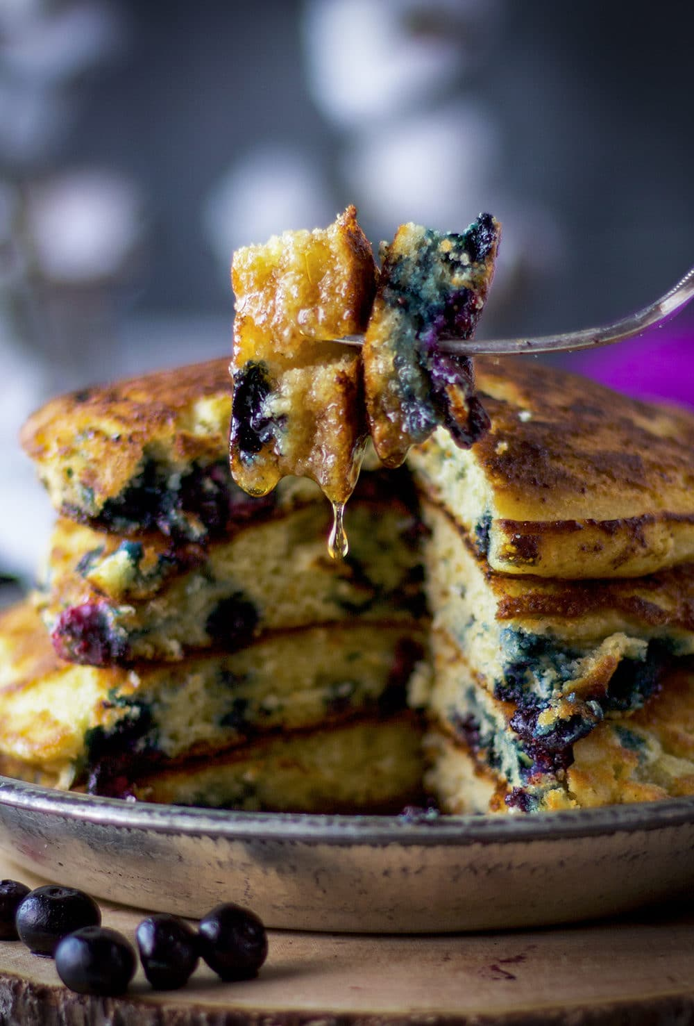 A bite of blueberry pancakes with maple syrup dripping from the fork.