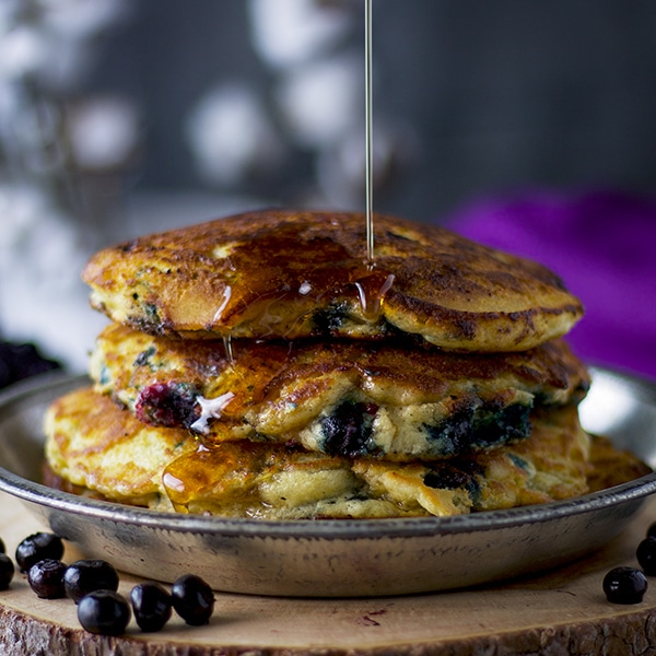Pouring maple syrup over a plate of fluffy blueberry pancakes.