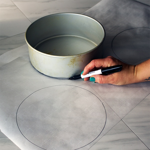 Tracing the bottom of cake pans to cut out parchment circles that will line the bottom of the pans.