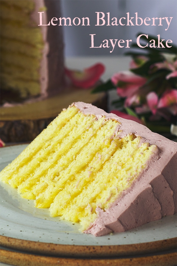 A slice of Lemon Layer Cake with Blackberry Italian Meringue Buttercream