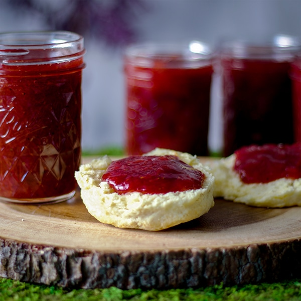 Strawberry rhubarb jam spread on a biscuit with several jars of jam.