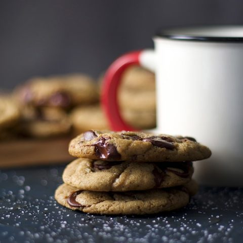 A stack of soft chocolate chip cookies and a mug of milk.