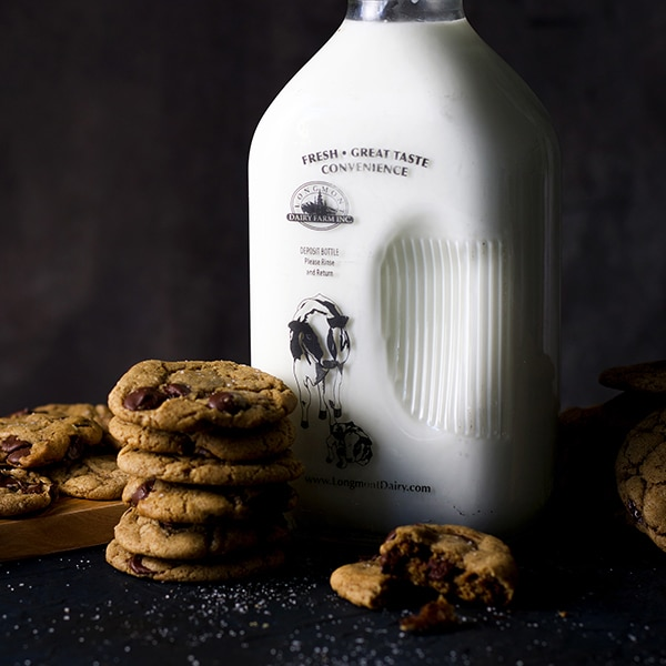 A stack of soft chocolate chip cookies and a bottle of milk.