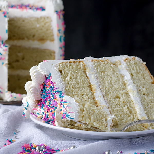 A slice of Gluten Free Vanilla Cake with Italian Meringue Buttercream