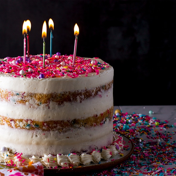 Funfetti Cake with Classic American Buttercream topped with lit birthday candles.