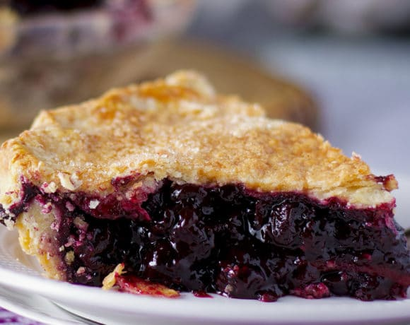 A freshly baked slice of homemade blueberry pie on a plate, ready to eat.
