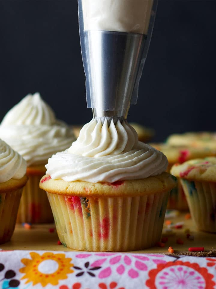 Piping American Buttercream onto Cupcakes