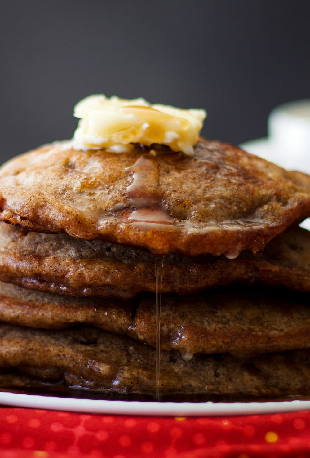 A stack of Apple Cinnamon Pancakes with butter and maple syrup.