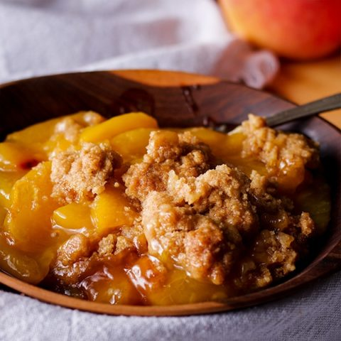 A bowl of peach cobbler with brown sugar cookie crust.